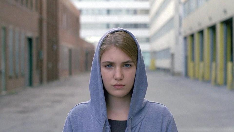 Une jeune fille, la tête sous une capuche.