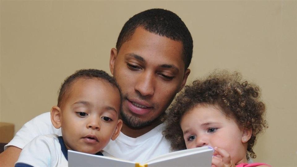 Un père lit avec ses enfants.