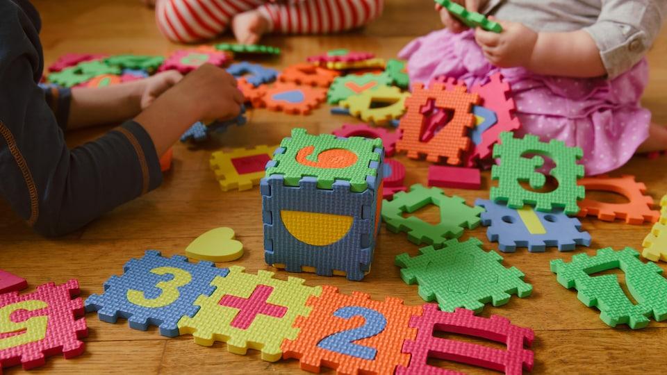 Des enfants jouent avec des blocs en mousse.