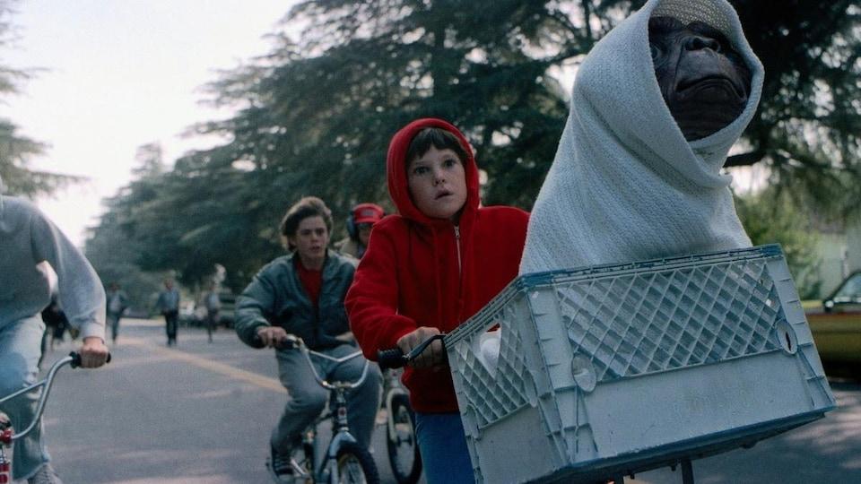 Un petit garçon sur son vélo, avec un extra-terrestre dans son panier