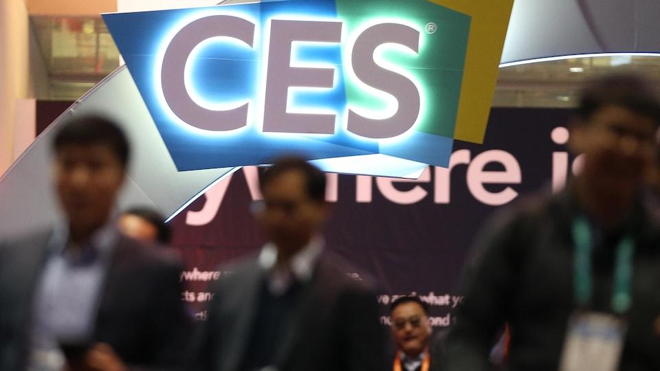 Des participants se déplacent dans le centre de congrès. Les lettres CES sont en haut au centre de la photo.