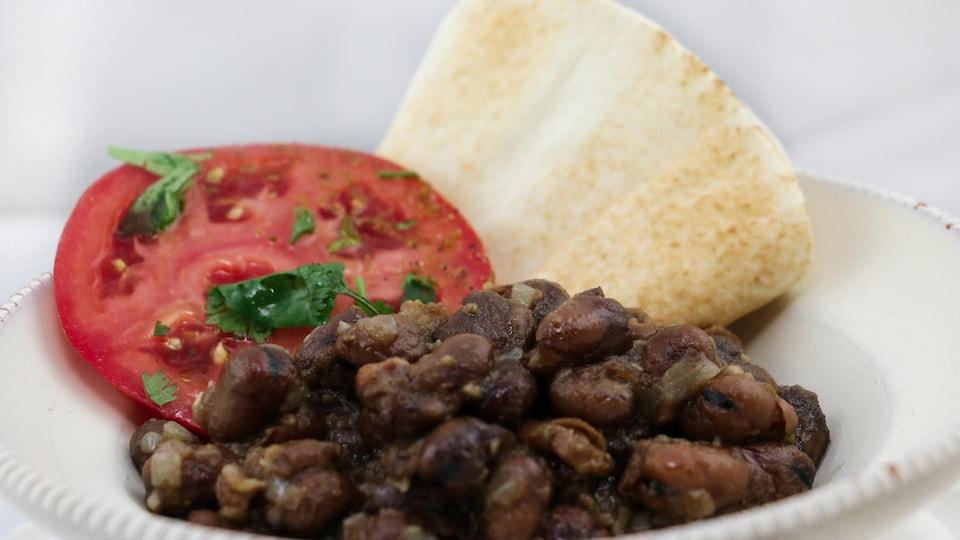 Le plat contient des haricots assaisonnés accompagnés d'une tranche de tomate et de pain pita.