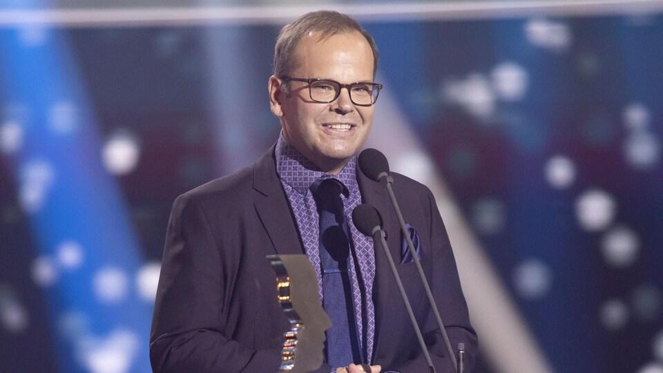 L'acteur sur la scène avec son trophée.