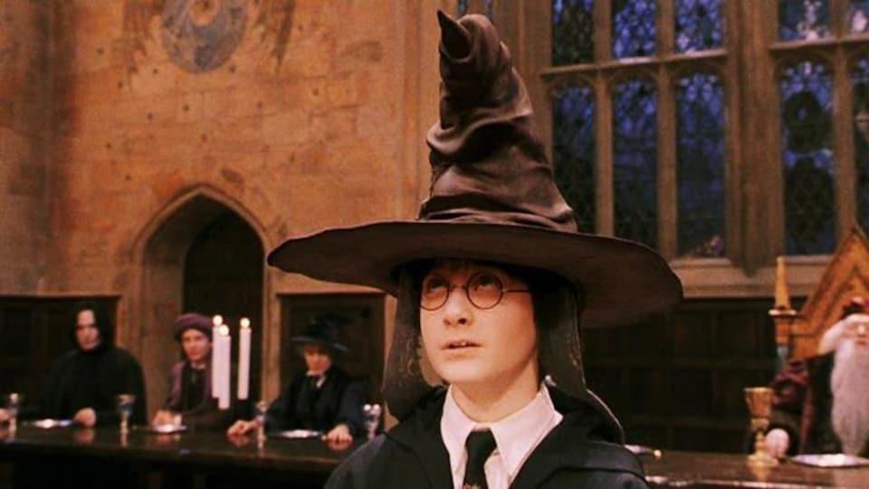 Un jeune garçon (Daniel Radcliffe) porte un chapeau pointu sur la tête.