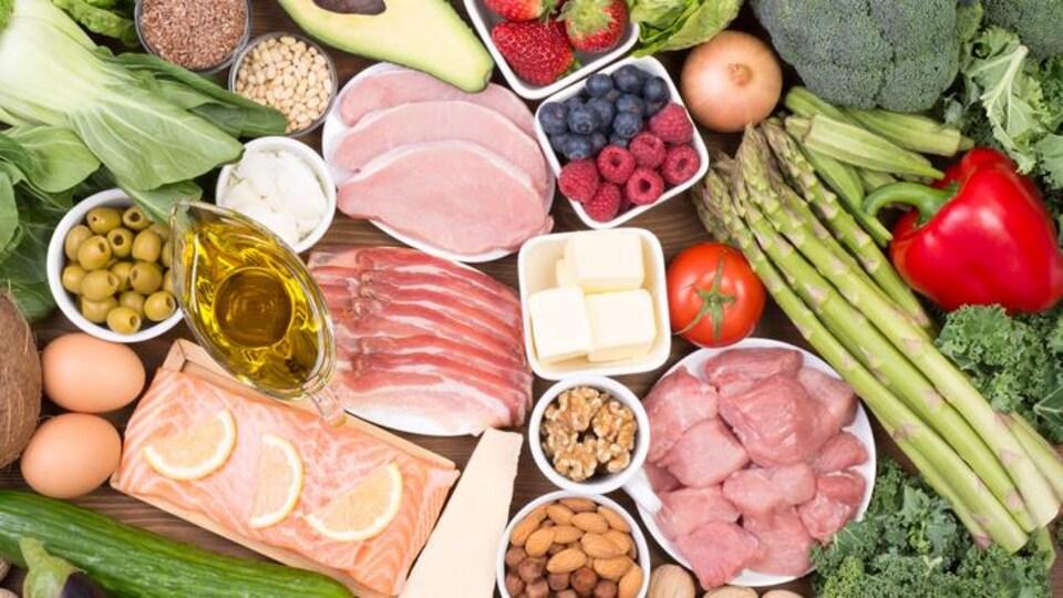 Plusieurs aliments, tels que du poisson et de la viande rouge, sont disposés sur une table en bois.