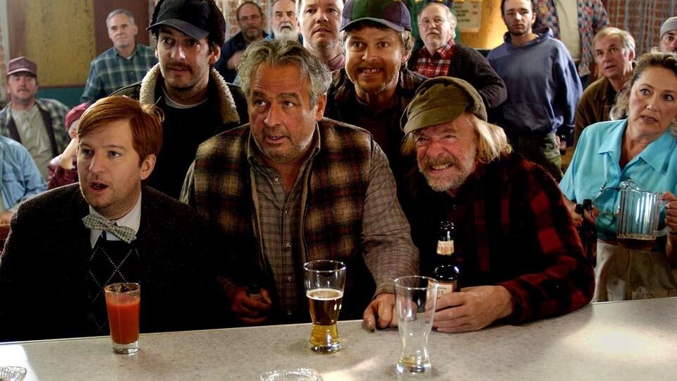 Des hommes attablés à un comptoir de bar, l'air nerveux