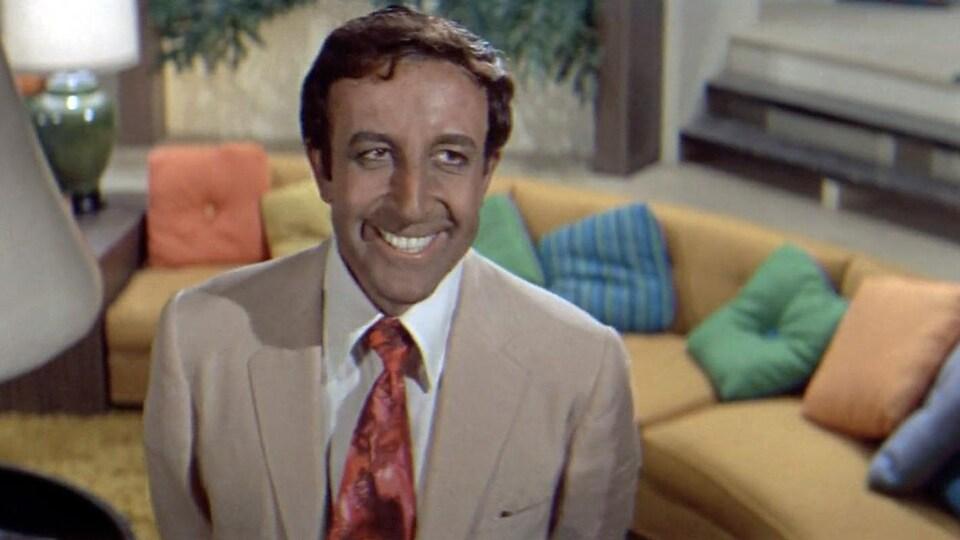 Un homme en costume, souriant, dans un salon.