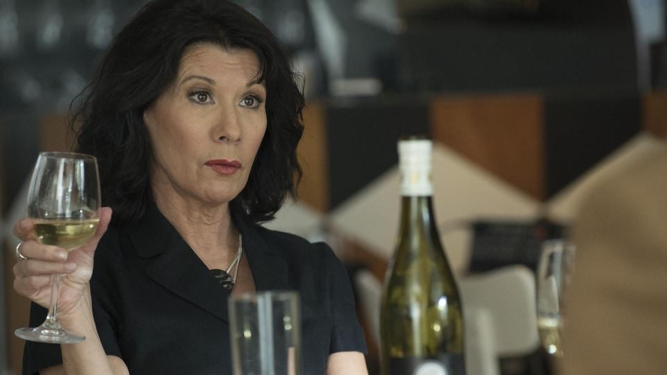 Madeleine dans Lâcher prise tient un verre de vin blanc dans sa main droite.