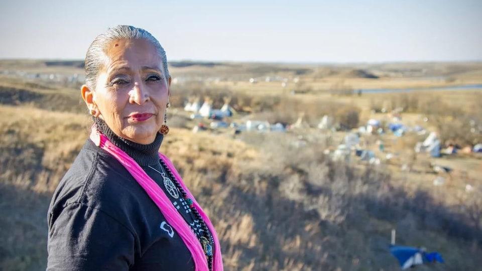 Une femme se tient dans une prairie.