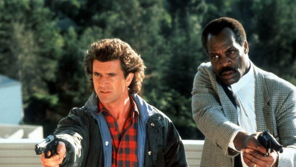 Mel Gibson et Danny Glover tiennent chacun un pistolet dans la main.