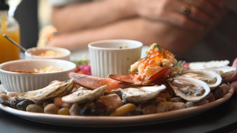 Gros plan sur une assiette gastronomique d'huîtres et de pinces de homard.