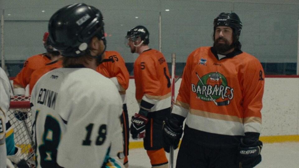 Un joueur de hockey (Philippe-Audrey Larrue St-Jacques) avec le chandail orange des Barbares de la Malbaie, sur la glace.