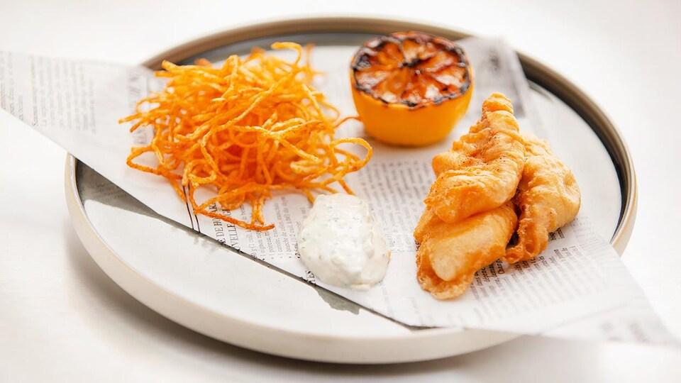 Une assiette de Fish and chips de truite arc-en-ciel avec un citron confit.