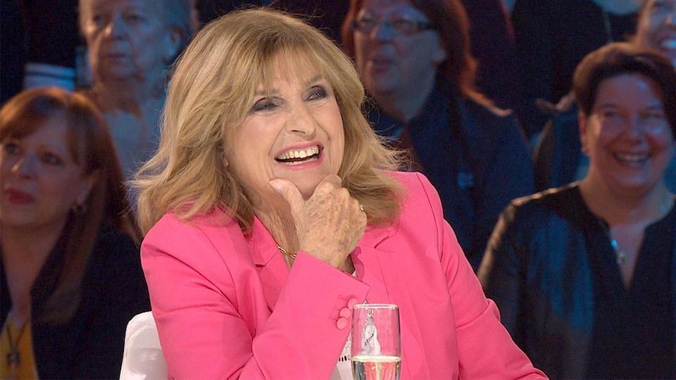 La femme est assise derrière une table sur un plateau de télévision. Elle porte un chemisier rose.