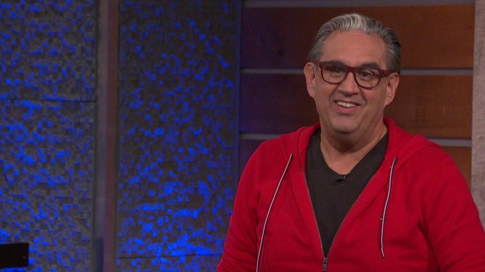 Il porte des lunettes et une veste à capuchon.