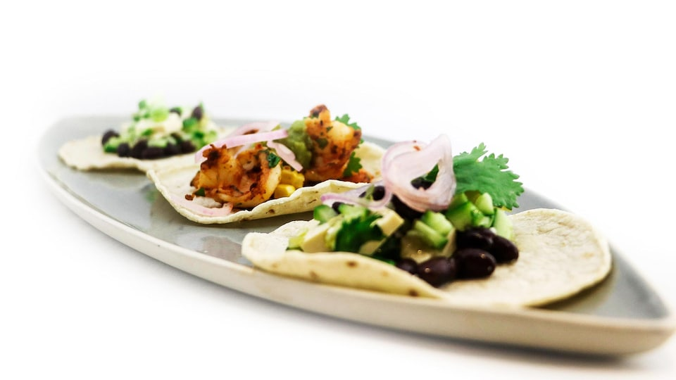 Trois tacos dans une assiette.
