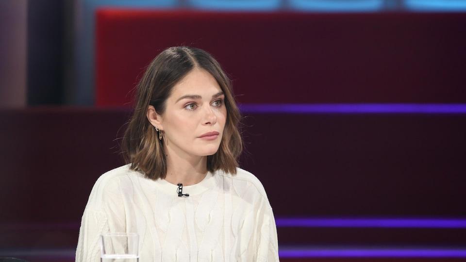 La femme habillée de blanc est assise dans un studio de télévision et regarde l'animateur qu'on ne voit pas.