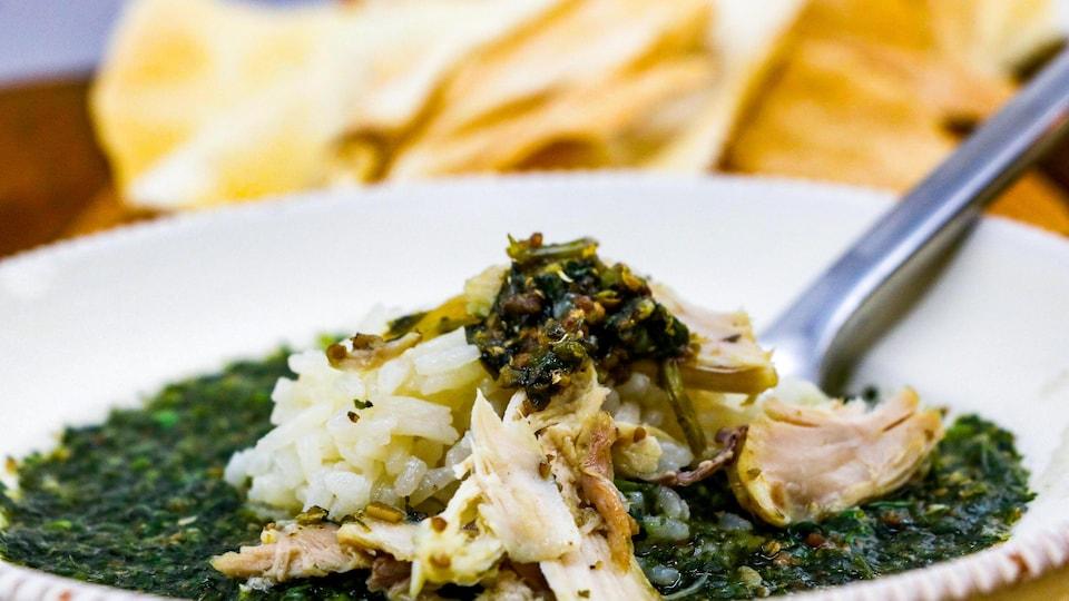 Une soupe avec du poulet, des oignons, de l'ail et des épices.