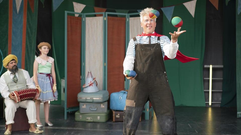 Sur une scène extérieure, un homme (Patrick Huard) maquillé en clown jongle devant un autre homme portant un turban et jouant de l'accordéon (Robin Aubert) et une petite fille (Jasmine Lemée).