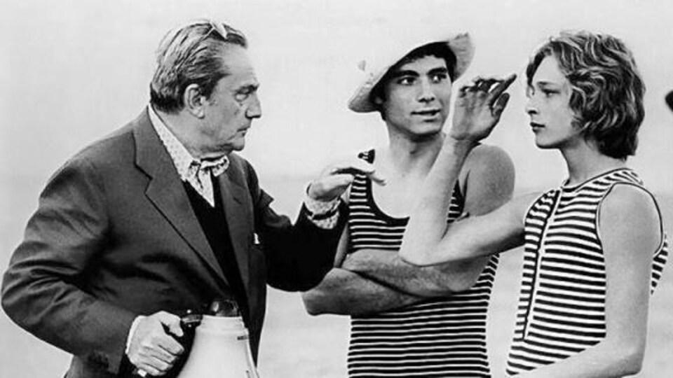 Le réalisateur en habit pointe les deux acteurs en grenouillère du doigt.