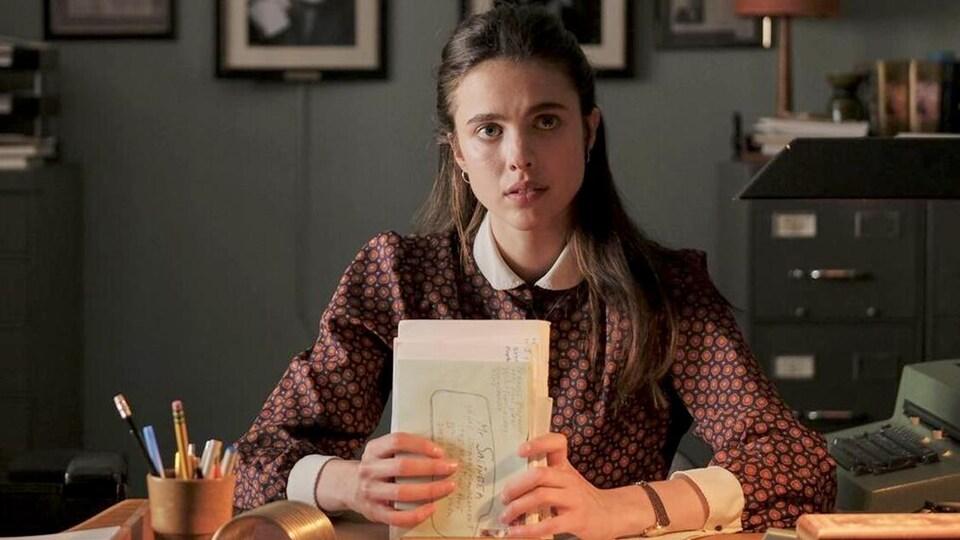 Une jeune femme (Margaret QUalley) assise à un bureau, des lettres entre les mains.
