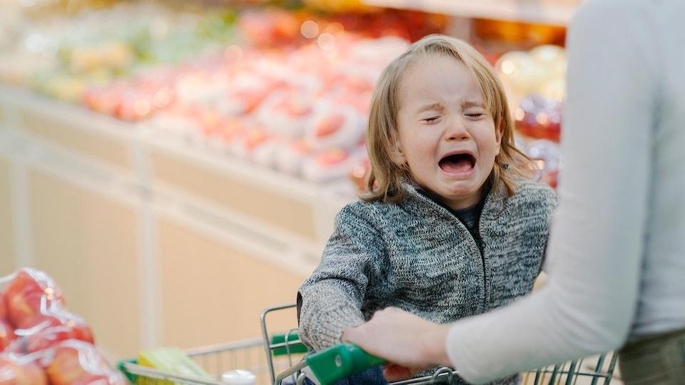 Un jeune enfant dans le chariot pleure fort alors que sa mère essaye de faire son épicerie.