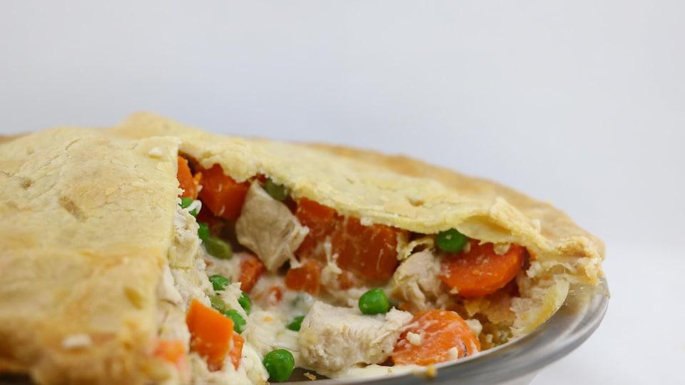 Une pointe a été coupée. Le pâté contient du poulet, des pois et des carottes.