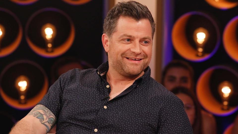 L'humoriste porte une chemise à manches courtes noire à petits motifs blancs.