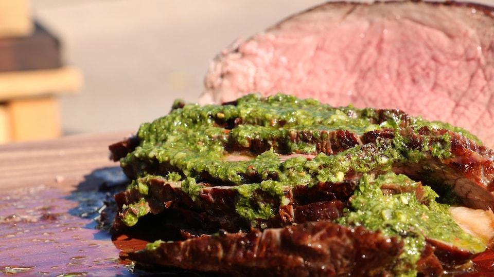 Des tranches de boeuf avec de la sauce aux herbes déposée sur la viande.