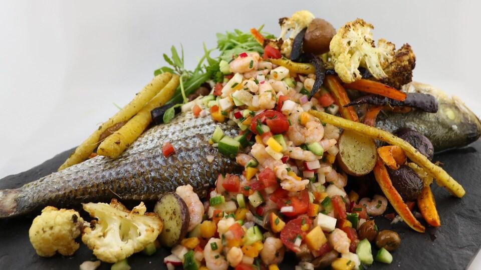 Le poisson, entier, est recouvert de crevettes nordiques et de légumes.