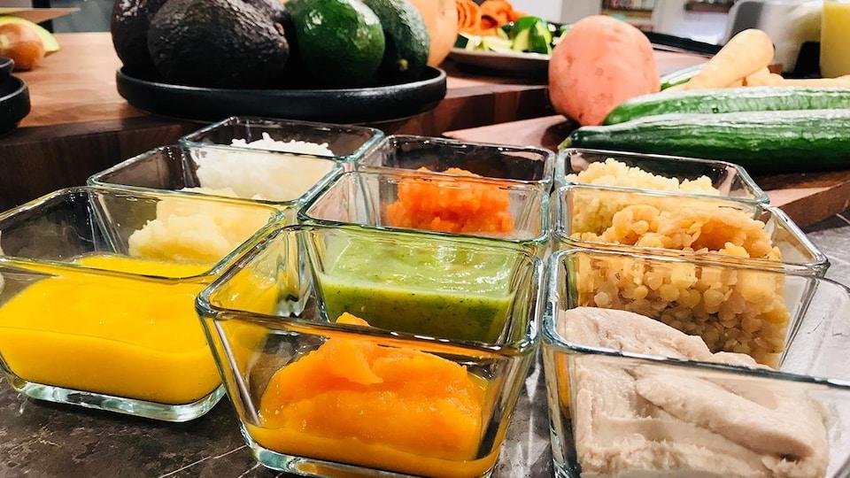 Des plats transparents contenant du jus d'orange ou des purées de patates douces, de poisson blanc, d'avocat ou de tofu