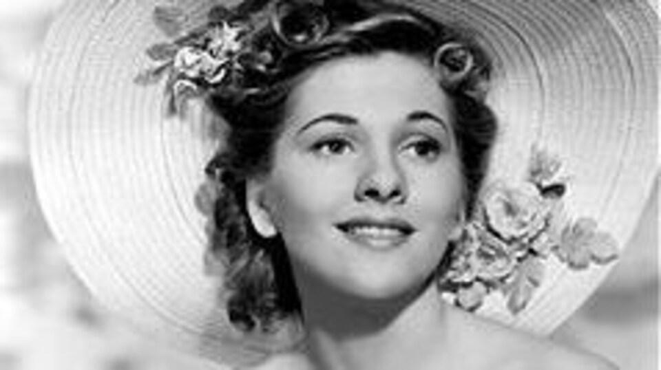Joan Fontaine sourit, un chapeau sur la tête.