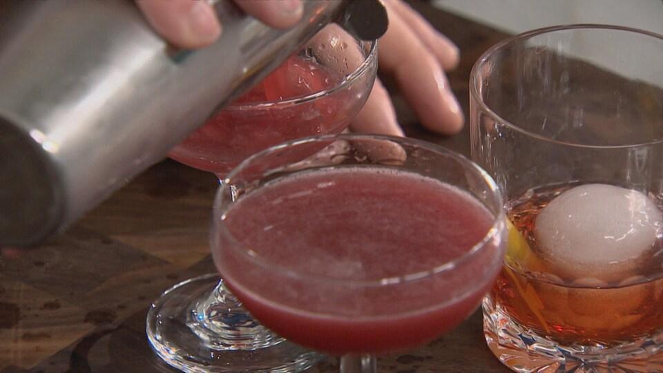 Patrick Huard verse les cocktails dans les verres.