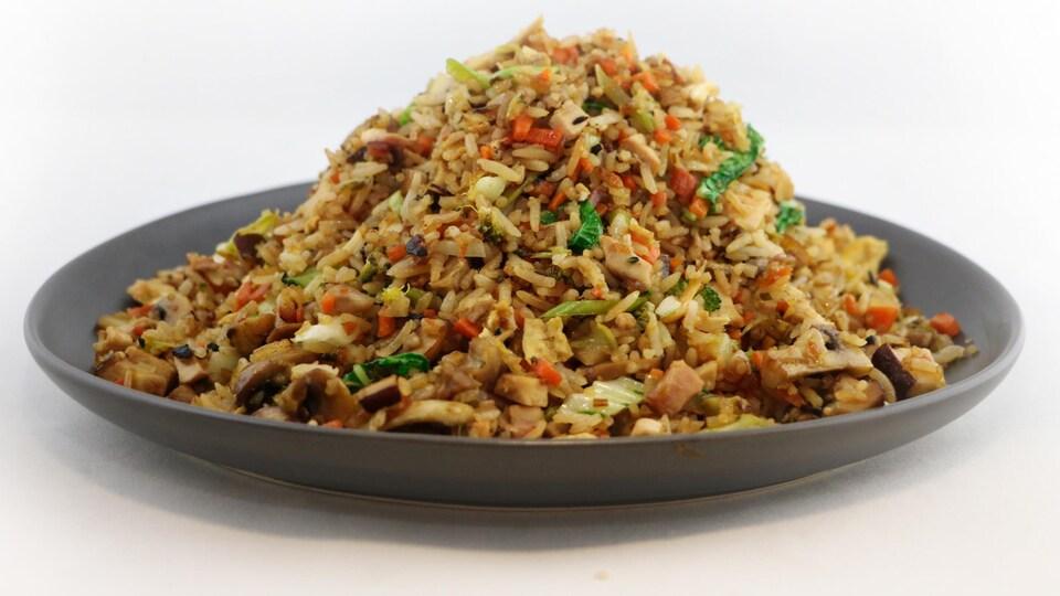 Le riz est composé de carottes, de poivrons, de champignons, d'oignons et de poulet.