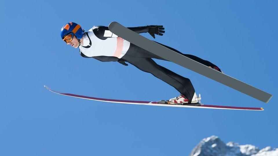 Son corps et ses skis sont parallèles. Sur fond de ciel bleu.