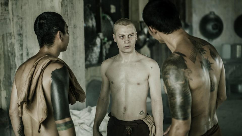 Un jeune homme torse nu (Antoine Olivier Pilon) est entouré de deux jeunes hommes torse nu et menaçants.