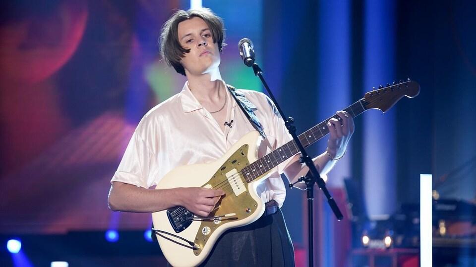 Un homme qui chante en jouant de la guitare.