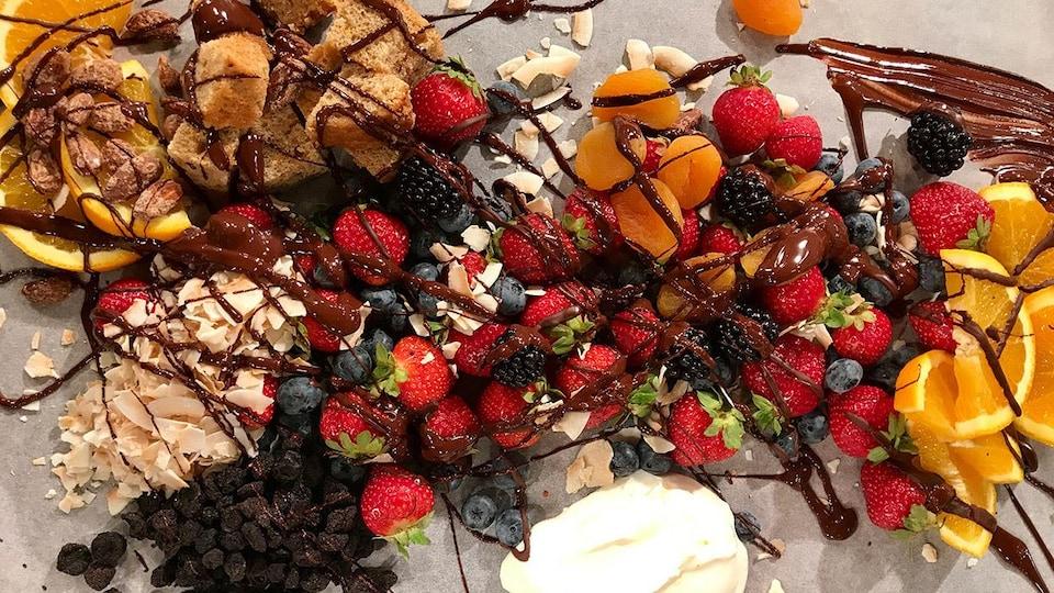 Des fraises, quartiers d'orange, bleuets et mûres recouverts de chocolat
