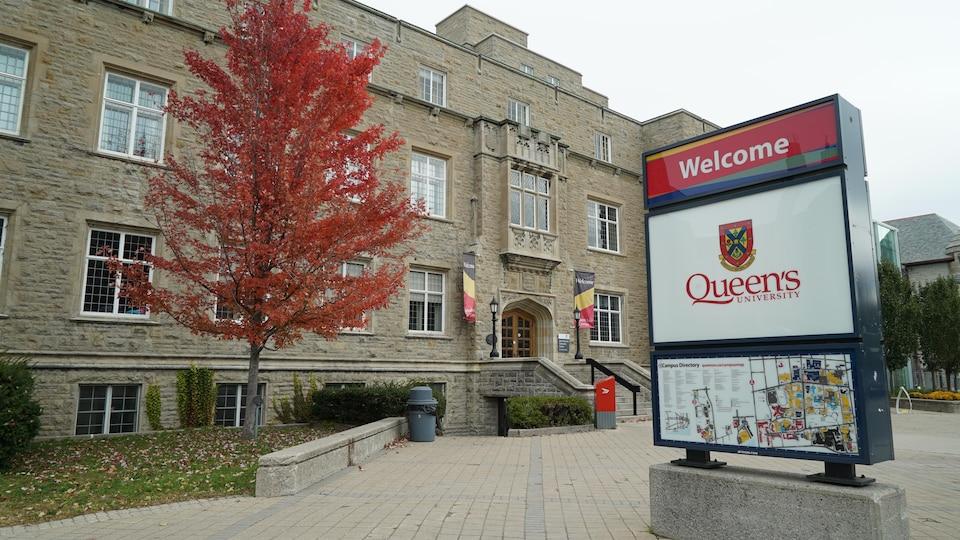 En avant-plan, l'affiche de l'université et un arbre aux couleurs automnales.