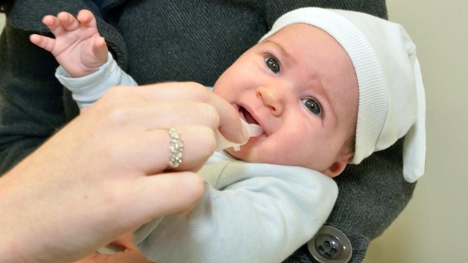 Une nourrisson reçoit un vaccin oral.
