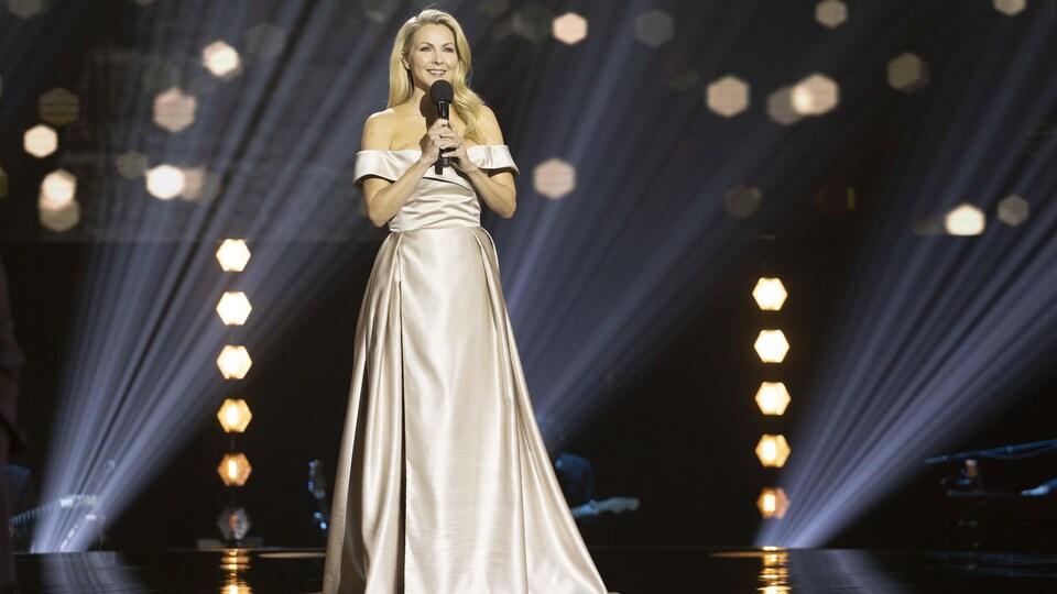 L'animatrice, sur scène dans une robe de soirée, tient un micro.
