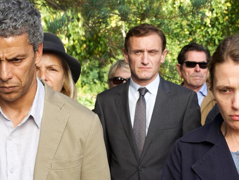 Un couple, le visage triste et fermé, et en arrière d'eux, un homme au regard froid, en costume sombre.