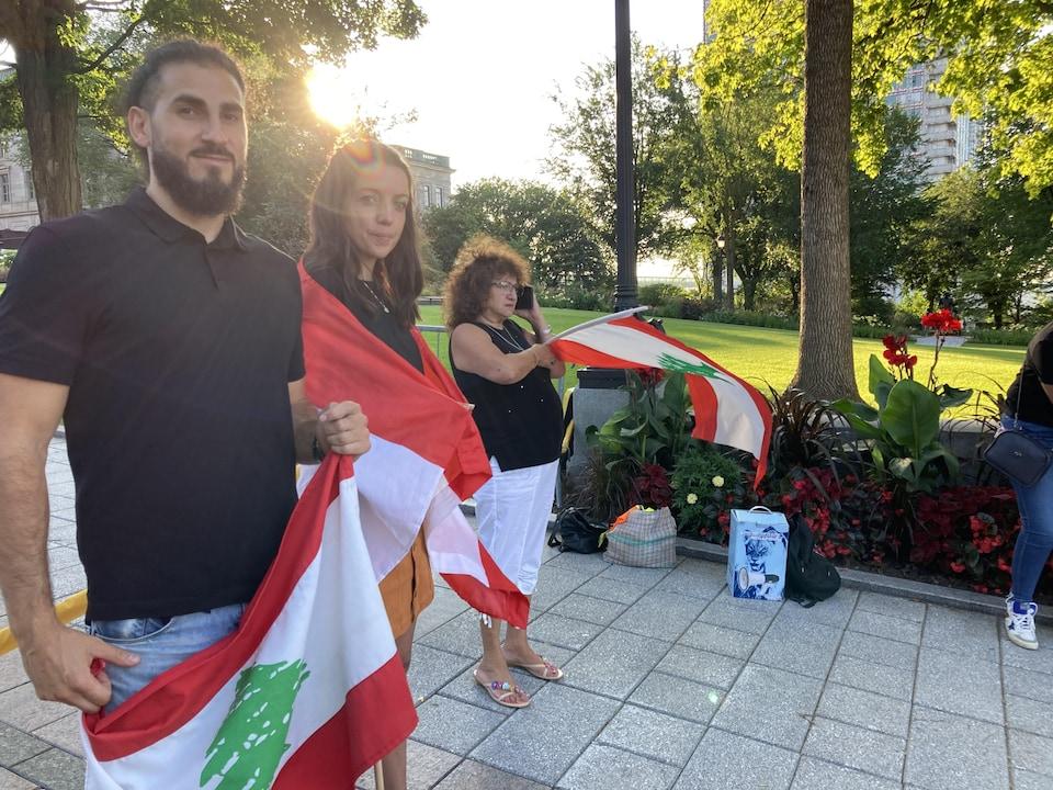 Deux personnes tiennent un drapeau du Liban autour d'eux. L'homme et la femme regardent la caméra. Ils sont à l'extérieur.
