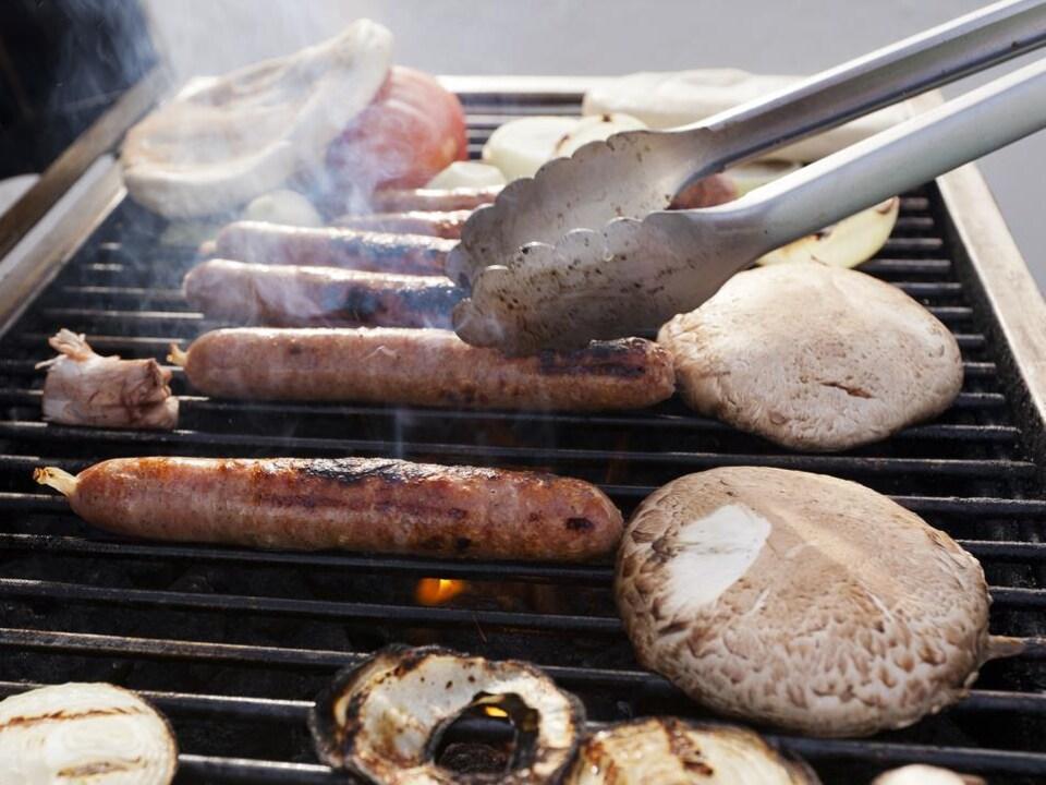 Des saucisses, champignons et légumes qui cuisent sur le barbecue.