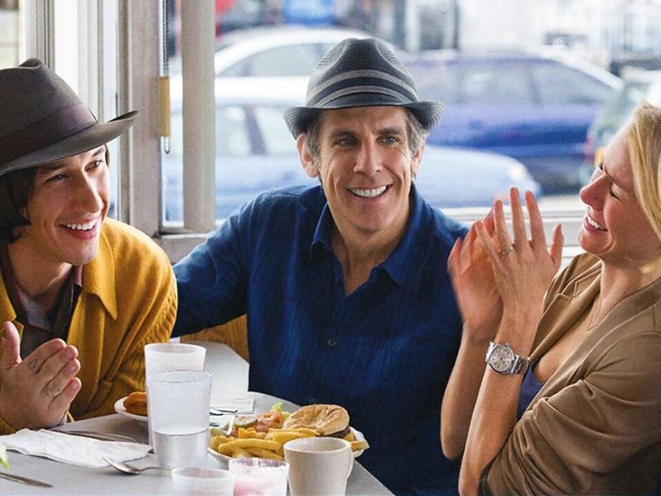 Un couple de quadragénaires et un couple de vingtenaires assis ensemble dans un restaurant.
