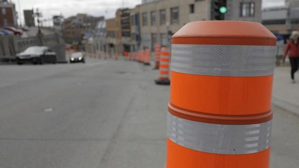 Cône orange en avant-plan, avec des voitures et un piéton à l'arrière.