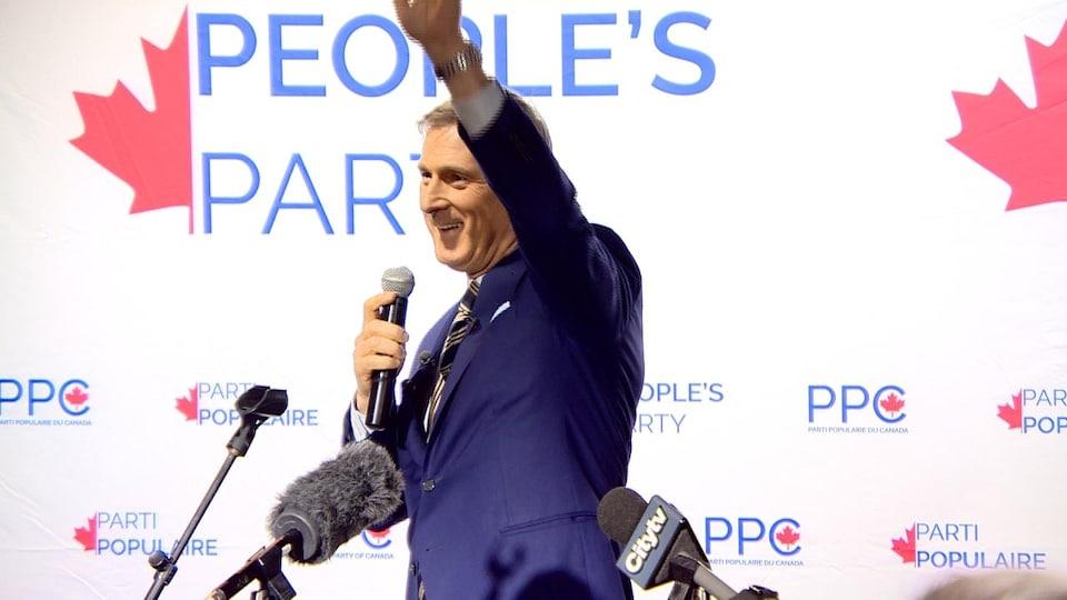 Maxime Bernier devant une affiche de son parti.