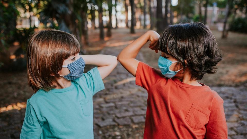 Deux enfants se saluent avec avec le coude et portent un masque.