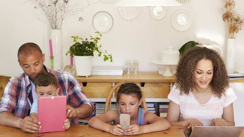 Une famille réunie autour d'une table, derrière des tablettes.