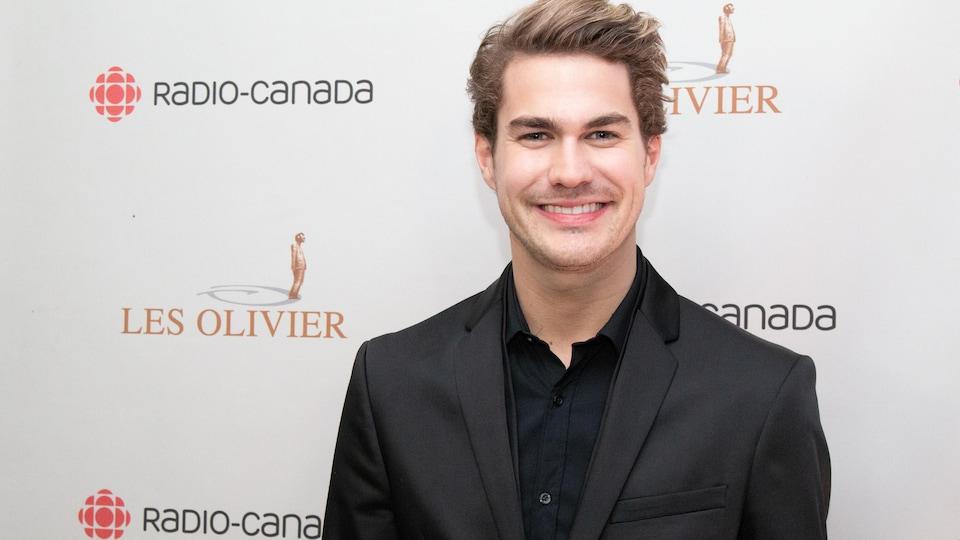 Il sourit sur le tapis rouge du Gala Les Olivier